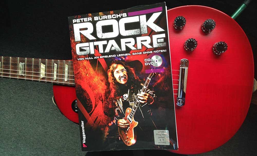 Instrument, Buch, Verstärker (nicht im Bild) und eine Portion Ehrgeiz – dann klappt's auch mit der Gitarre!